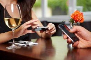 Hände mit Handys im Restaurant